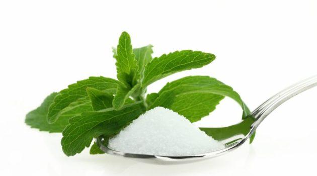 Fresh Stevia Rebaudiana and sugar in a spoon